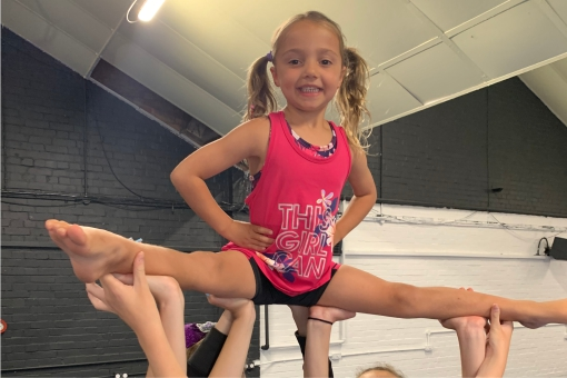 Young girl doing a straddle stunt