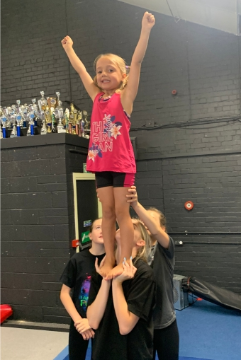 Young girl performing a cheerleading stunt