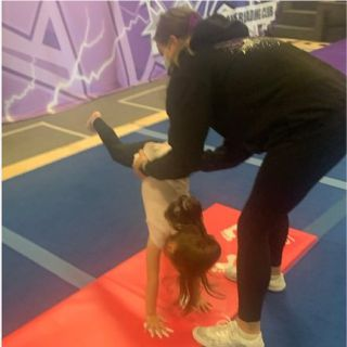 A young girl is enjoying learning gymnastics skills at a Cheer for Fun Preschool session