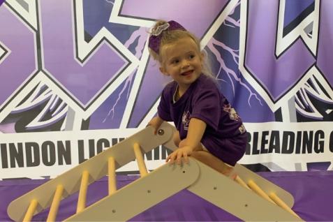 Young girl on a climbing frame enjoying Toddler Tumble