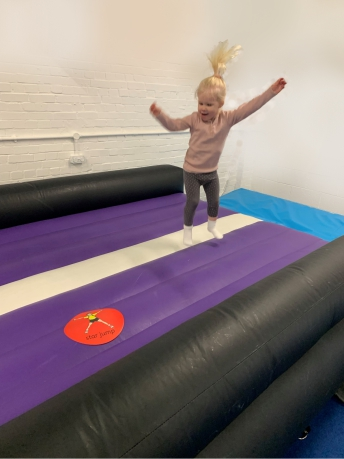 Toddler enjoying bouncing on the air track