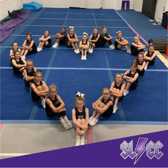 Youth team members sat in a heart shape in the gym